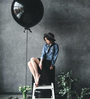 woman-sitting-on-chair-beside-balloon-1391580